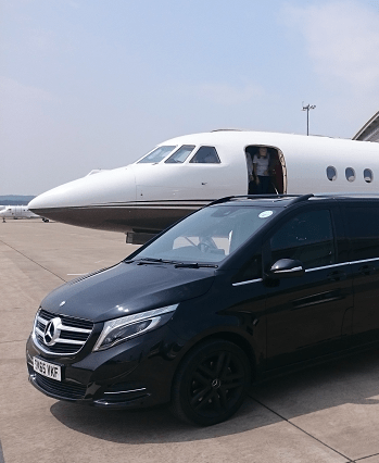 chauffeured mercedes v-class in front of a private jet